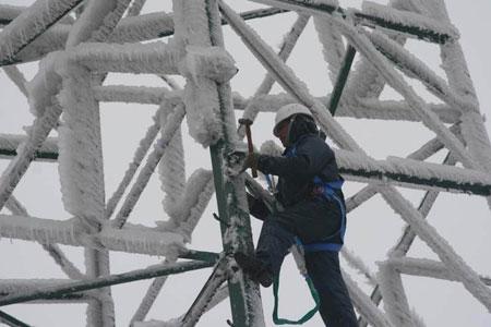 图为:维修人员在清除基站上的冰霜